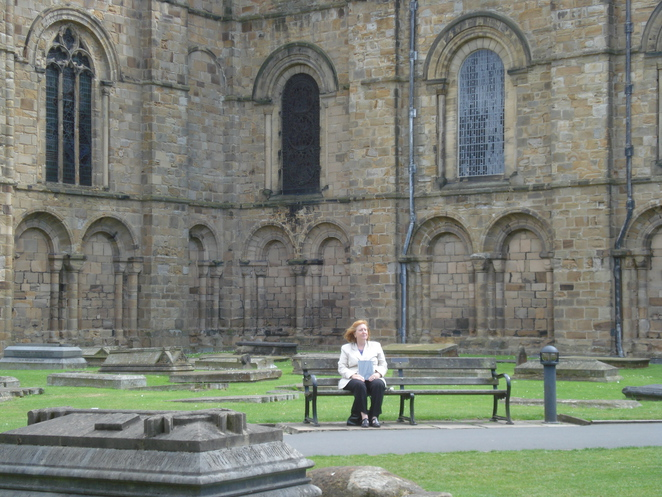 Margaret reads her souvenir booklet on Palace Green outside Durham Cathedral