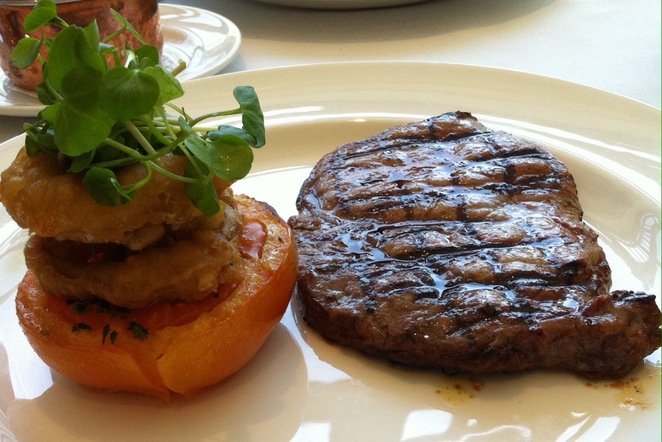 8oz rib eye steak with grilled tomato & onion rings @ Marco Pierre White Steakhouse Bar & Grill